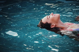 image of a woman floating in the water. You need to get comfortable when you learn to swim