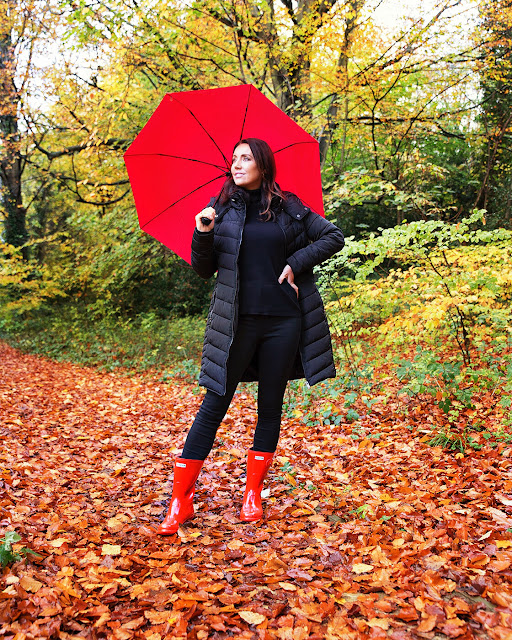 Black coat with red wellies and red umbrella