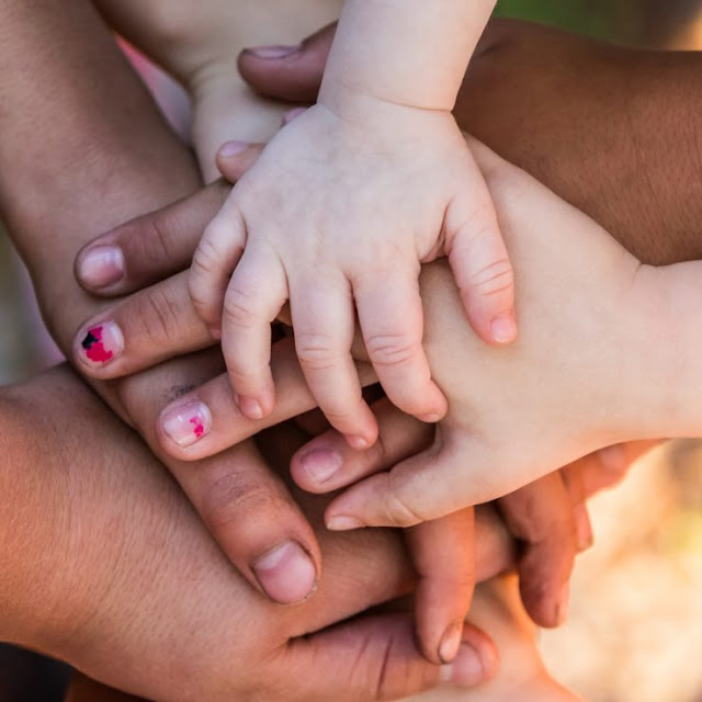 Different sized hands of different races piled on top of one another