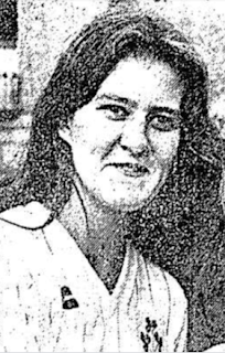 Black and white photo of a smiling woman with long dark hair