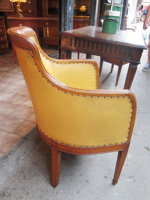Close up of the back and side of one of the the 17th century antique petite barrel side chairs upholstered in a mustard yellow leather like material