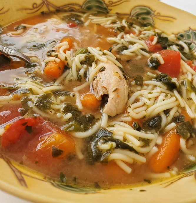this is a bowl of chicken soup with spinach carrots and cut up spaghetti