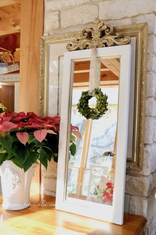 French country mirror layered in front of a gold-framed everyday print adds Christmas style