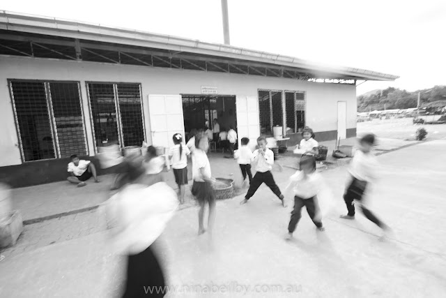 Outside the schoolroom, the children play. This photo shows one boy standing and the others are blurred as they run around him.