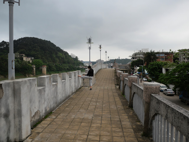 young woman stretching on a wall bordering the Gui River (桂江) in Wuzhou (梧州)