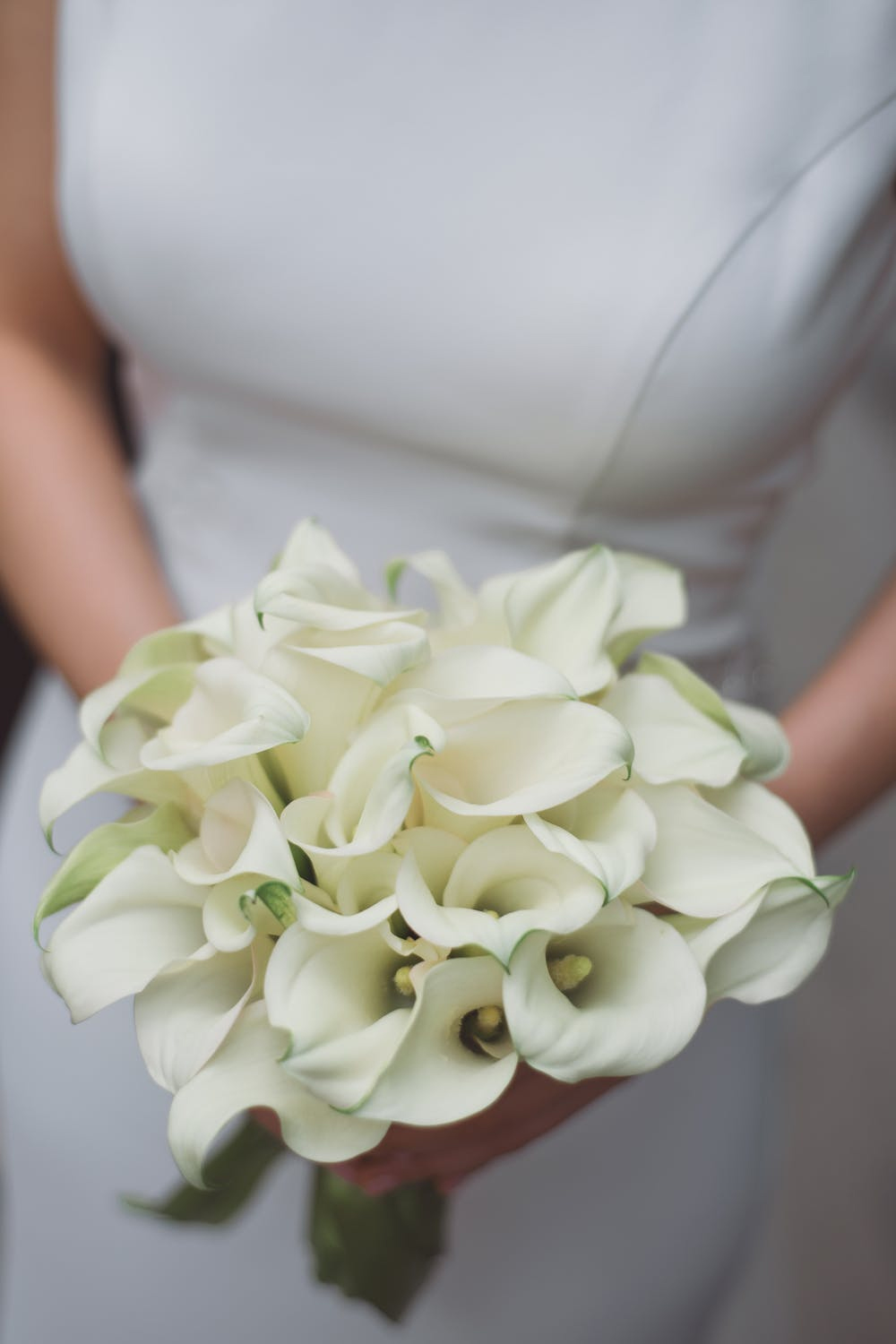 bride is holding bouquet of calla lilies