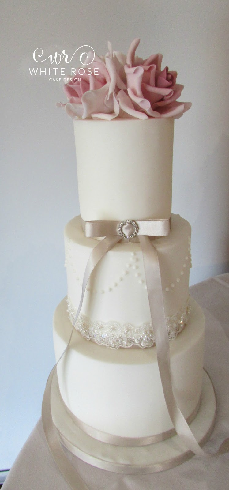 Wedding Cake Three Tiers With Crisp Edges Finished Sparkly Lace And A Brooch Piped Pearls On The Middle Tier Add Extra Interest