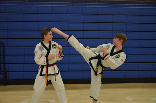 Two martial arts taekwondo black belts practicing one steps sparring