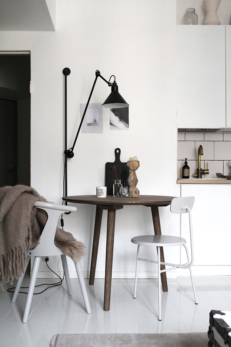 How to light a dining room without a ceiling light, alternative dining room lighting ideas, lighting above the dining table, swing arm wall lamp above the dining table, long arm wall lamp in the dining room. Photo via Raw Design Blog