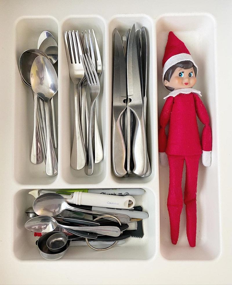 elf hiding in cutlery drawer