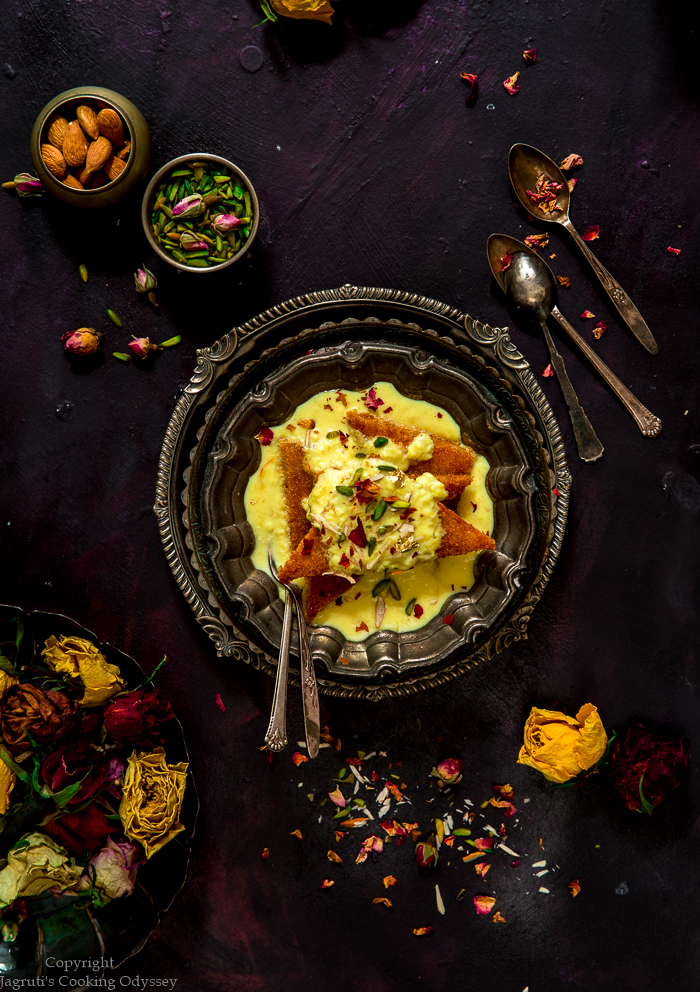 On a purple backdrop shahi tukda served in a bowl with spoon next to some yellow and red roses.