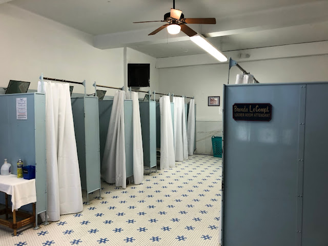 inside of a locker room with tiled floor and several changing stalls