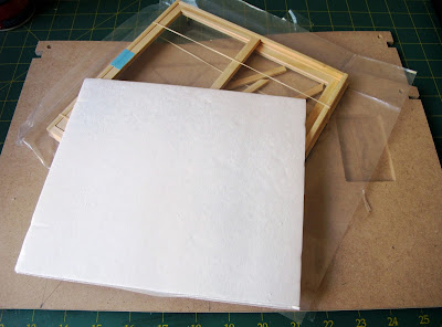 Pieces of a dollshouse building kit with a sliding door unit on top, covered with a piece of card.