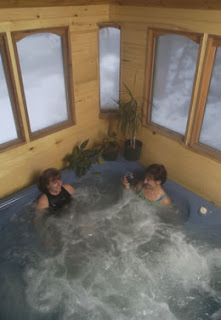 Two ladies sitting in the enclosed bubbling hot tub.