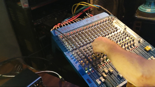 picture of a sound mixing board for music with arm turning a knob