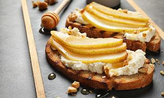 Crostini con queso, pera y rucula