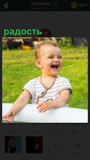 За столом сидит ребенок и радость его переполняет, он смеется и улыбается