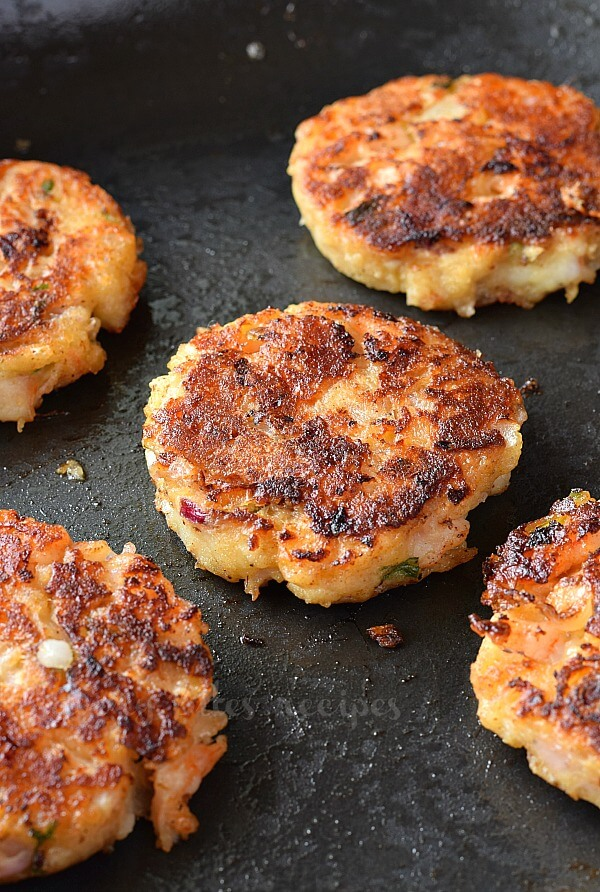 a close up of a skillet with shrimp cakes arranged