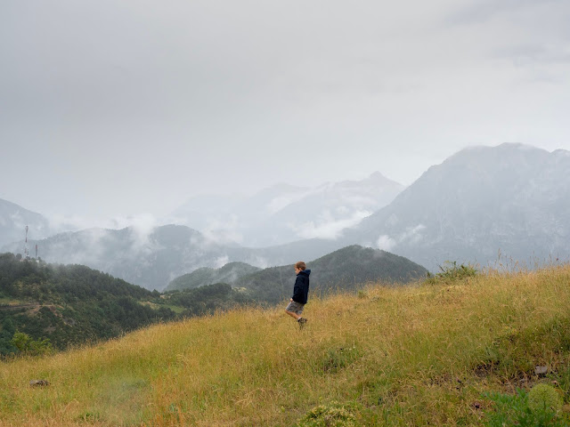 Niño caminando por una ladera con las montañas del fondo envueltas en niebla