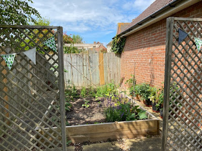 Vegetable patch with trellis entrance and bunting