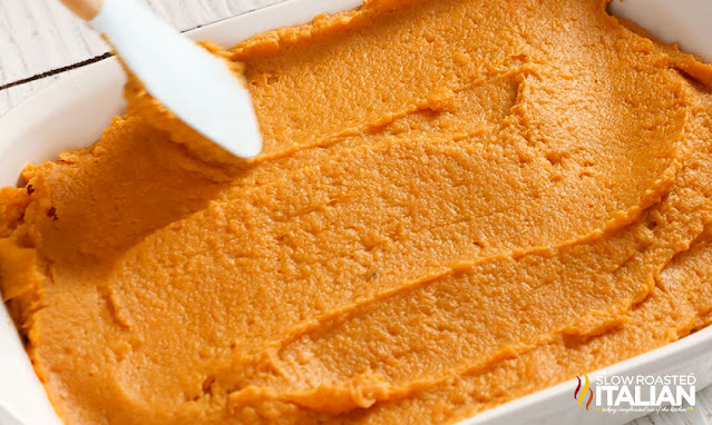 smoothing mashed sweet potatoes into casserole dish