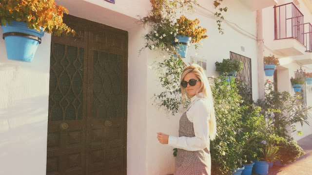 Alejandra Colomera frente una casa con macetas de flores