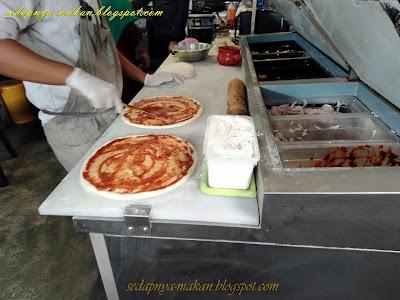 menyediakan piza sebelum dibakar menggunakan dapur kayu api