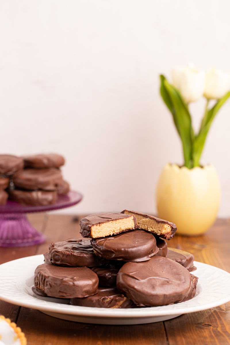 Photo of Keto Peanut Butter Chocolate Easter Eggs on a white plate with a platter of more eggs in the background.