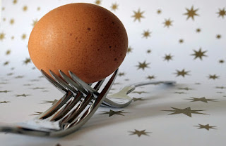 Brown egg resting on two forks