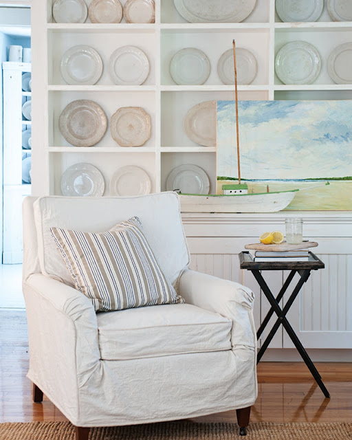 white slipcovered chair and antique ironstone plates