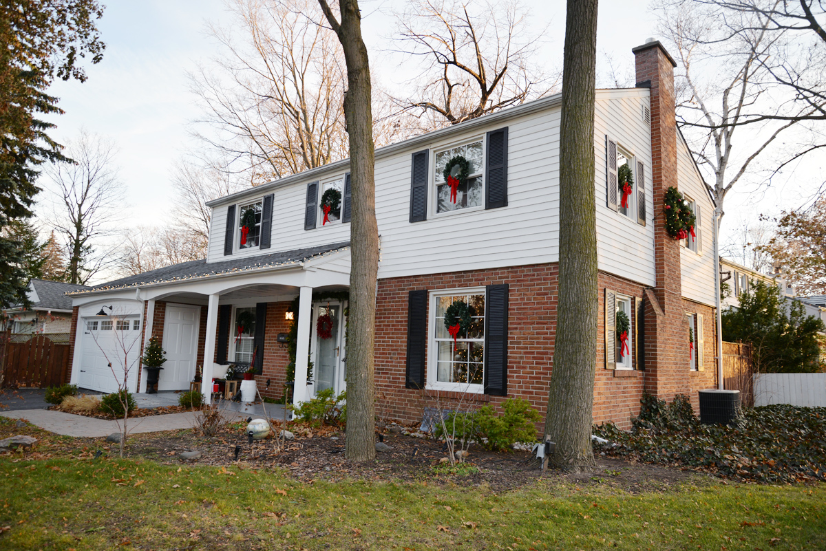classic christmas decorations, colonial house with wreaths on windows, wreaths on exterior windows