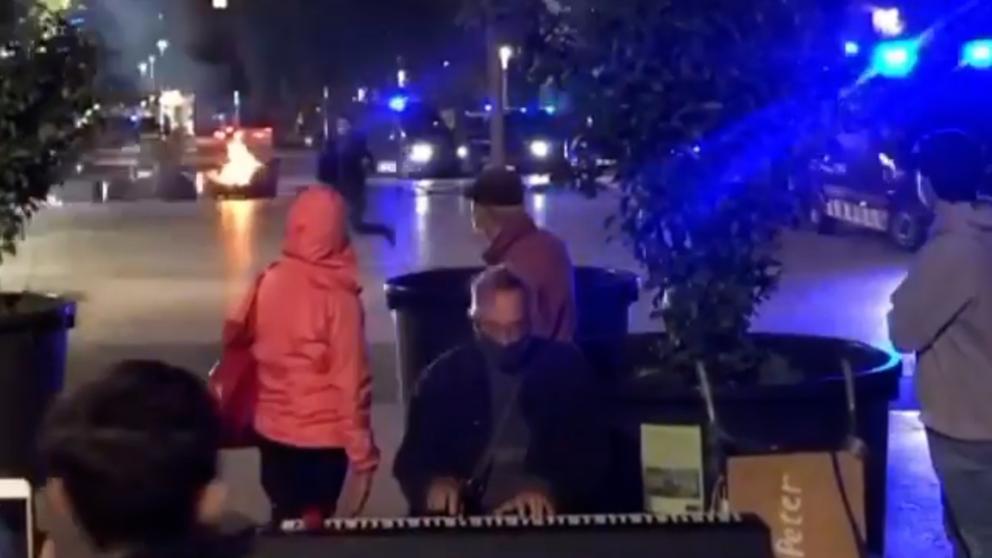 #VIDEO: Un pianista callejero toca con tranquilidad en #Barcelona con disturbios y llamas a su espalda