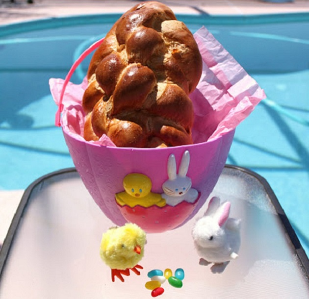Grandma's egg bread for Easter in an Easter basket with jelly beans and chicks in the photo near the pool outside