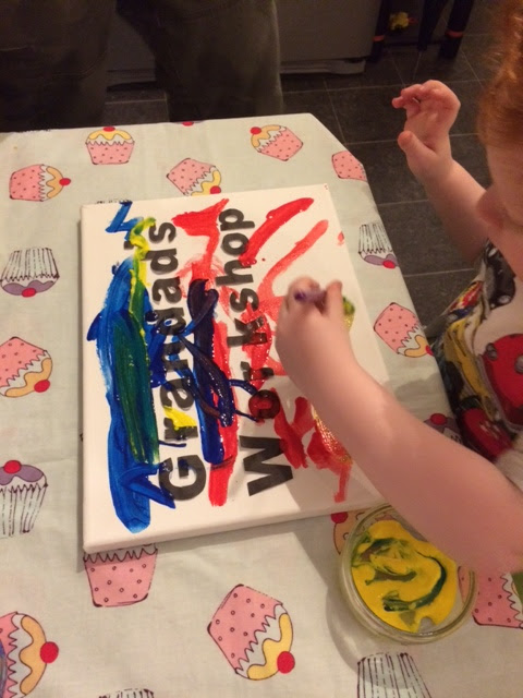 Toddler painting the canvas