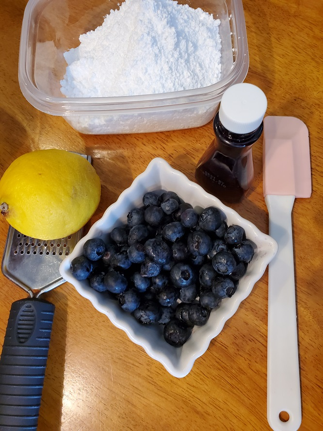 this is lemon zest and zester, blueberries and other tools needed to make blueberry drop cookies