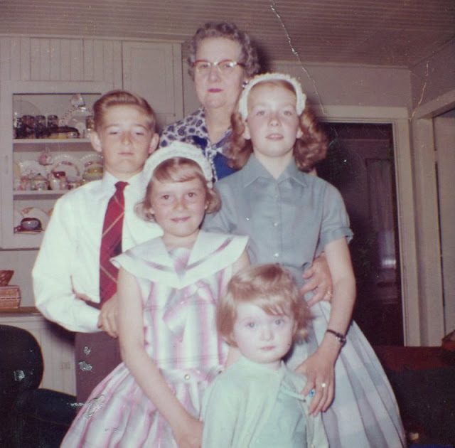 a grandmother, one young boy, two girls in Easter hats, and a small girl in a family portrait