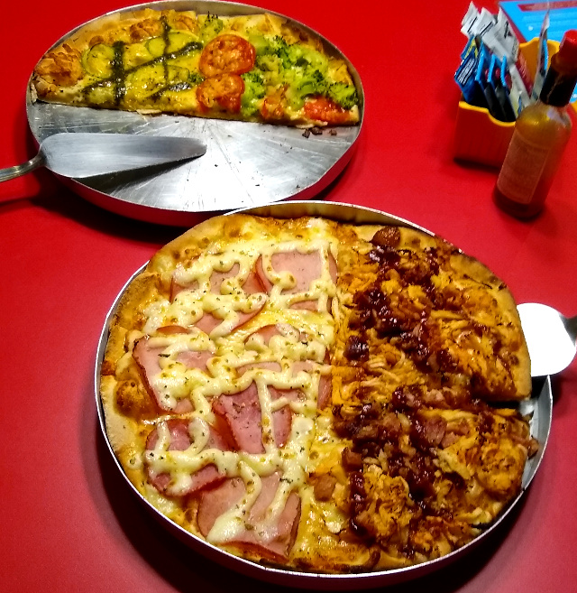 A zucchini small pizza and a larger pizza divided into two on with chicken and other with ham.