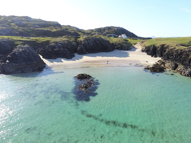 Bird's eye view of the secluded beach and crystal clear water at Clachtoll