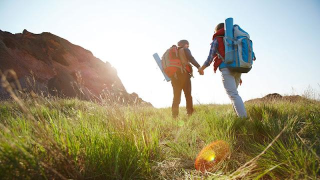 hiking couple holding hands through tallgrass