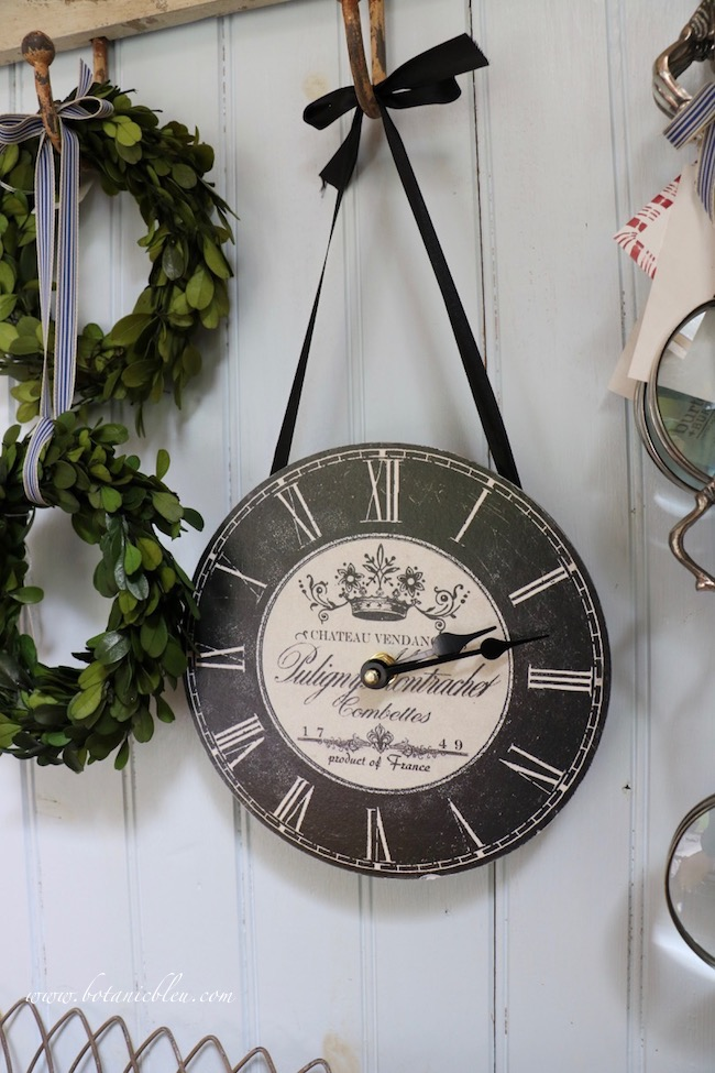 French Country is in the details of a black, French script decorated hanging wall clock