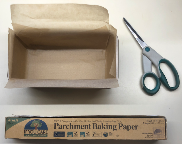 Photo of parchment paper lined loaf pan with box of baking parchment and scissors