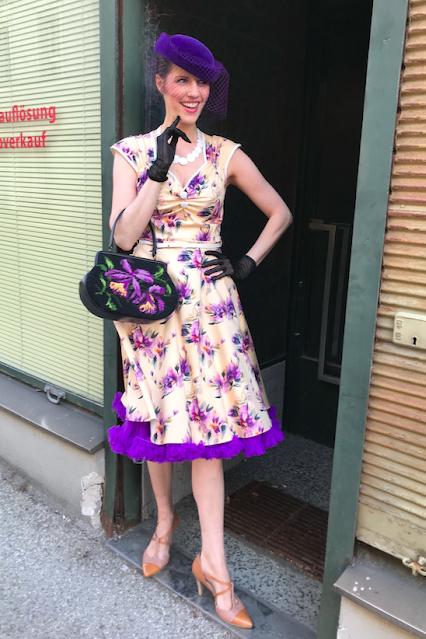 gudrun bluemel trägt das isabella dress violetta watercolour von lady vintage, eine dazupassende patit point tasche und einen lila hut mit Schleier