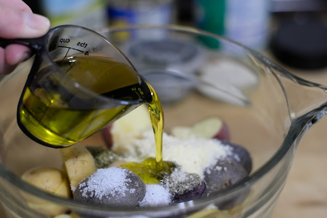 Extra virgin olive oil being poured over the potatoes and seasoning.