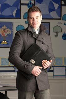Photo of a Young Man in a Coat Holding a Portfolio