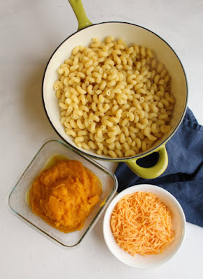 pan full of pasta with container of mashed acorn squash and cheddar for mac and cheese