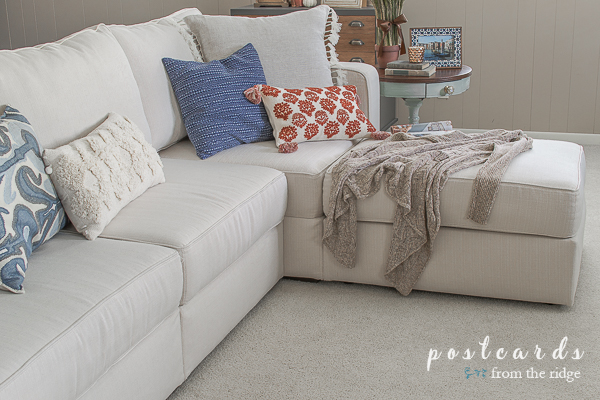 blue and orange fall pillows on an off white sectional sofa