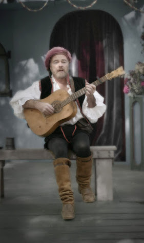 Hombre sosteniendo una citara medieval y cantando