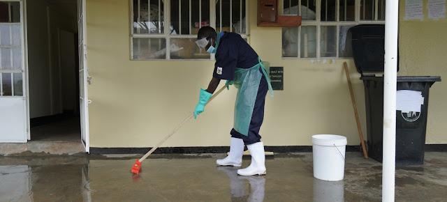 Un empleado de un centro de salud de Uganda limpiando el suelo con una mezcla de cloro y agua para prevenir infecciones. UNICEF/Michele Sibiloni