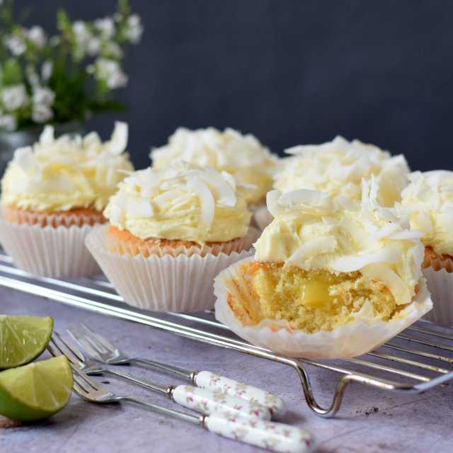 How to make Coconut and Lime Cupcakes  filled with lime curd and topped with a coconut buttercream frosting and toasted coconut flakes.