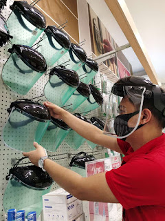 A staff of Ace Hardware arranges their display of helmet type face shields